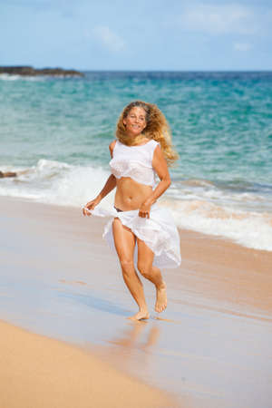 Beautiful Woman in her Forties running on the Beach in Hawaii photo