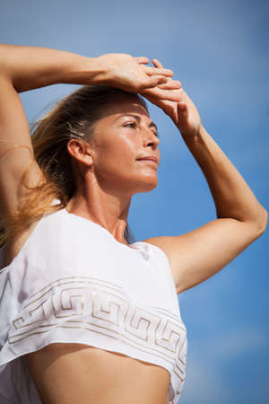 Beautiful woman with long hair in her Forties wearing a white sheer top against the Blue Sky photo