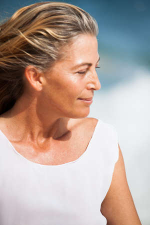 vejez feliz: Hermosa mujer de mediana edad que mira hacia fuera en la reflexión Foto de archivo