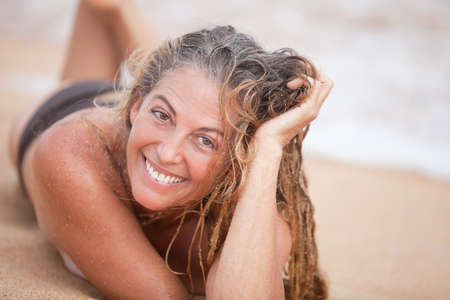 wet hair: Beautiful Smiling Woman lying on the beach with sandy wet hair