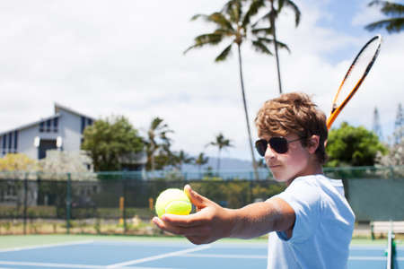Teenage Boy shows determination serving the tennis Ball in  Hawaii photo