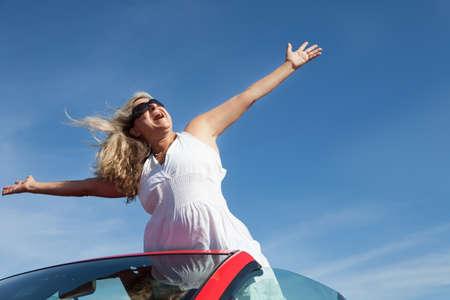 cabrio: Vrouw van middelbare leeftijd Loving Life uit de top van een converteerbare Stockfoto