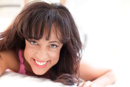 happy african woman: Pretty African American woman smiling at camera lying down