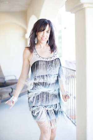 Happy Woman with a fringed dress dancing looking at camera photo