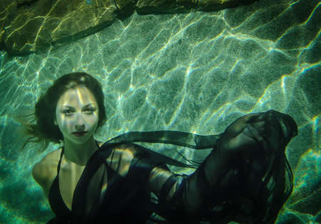 Beautiful young woman floating underwater in a black dress Stock Photo
