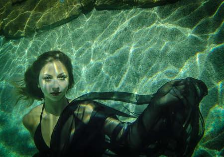 Mooie jonge vrouw drijft onder water in een zwarte jurk Stockfoto