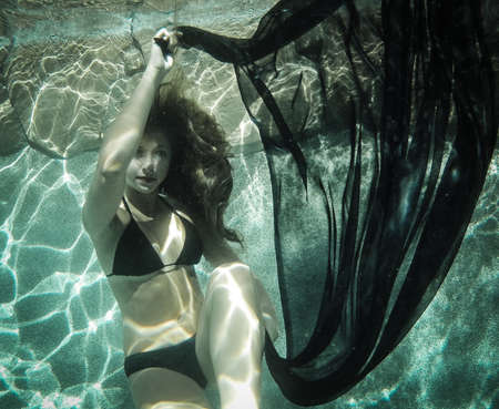 Pretty young woman floating underwater in a black Bikini photo