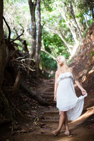 Pretty young woman in a white dress walking barefoot in nature photo
