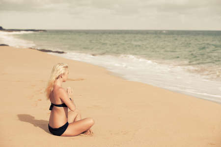Beautiful Blonde sitting in the Quiet of the Beach in prayer pose photo