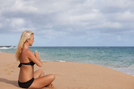 Beautiful Tanned woman sitting in the Quiet of the Beach in Meditation Stock Photo - 15041670