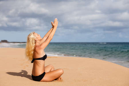 sun drenched: Sun drenched Blonde sitting in the Quiet of the Beach in Prayer Stock Photo