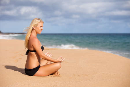 Beautiful Young Blonde sitting in Graditude at the Beach ending Meditation with Namaste photo