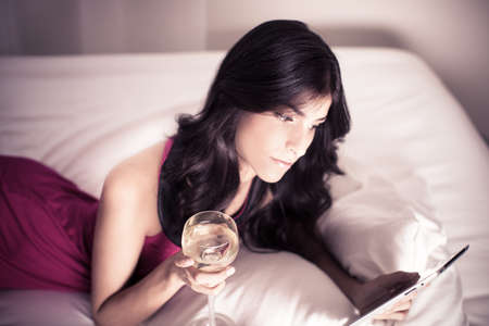 digitized: Beautiful Brunette curled up on the internet enjoying a glass of wine Stock Photo