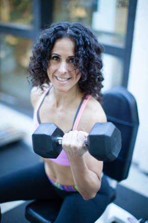 Fitness woman in her forties holding a 15 pound dumbbell