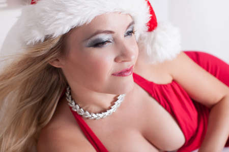 Beautiful Woman in a Santa Claus Hat and Sexy red dress photo