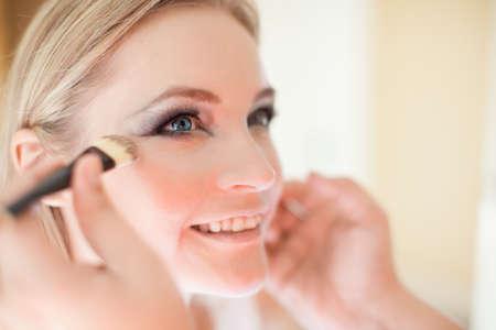 mujer maquillandose: Novia hermosa joven con maquillaje de la boda por el artista de maquillaje Foto de archivo