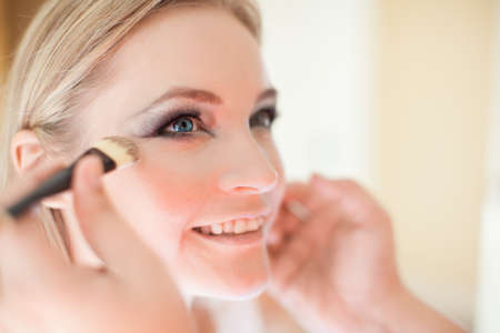 bridal dress: Young beautiful bride having wedding make-up by make-up artist Stock Photo