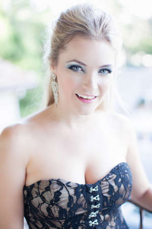 lacey: Beautiful Woman outside wearing a black lacey corset smiling at camera Stock Photo