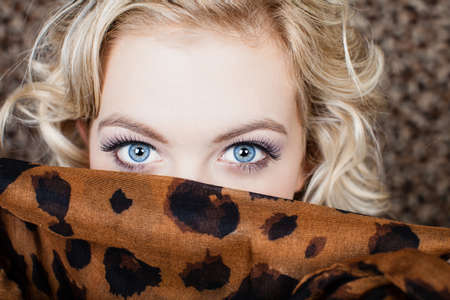 Beautiful Blonde womans eyes and scarf covering her mouth Stock Photo