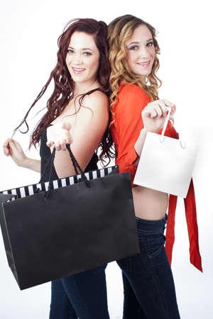 alike: Gorgeous women Smiling holding shopping bags isolated on white Stock Photo