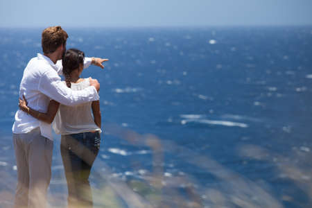 hugging couple: Man and woman looking out over the ocean pointing Stock Photo