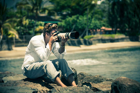 photographing: Man itting on Lava rocks taking pictures in Hawaii