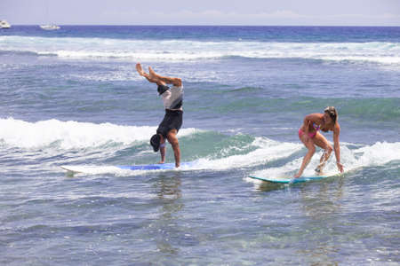 Friends Surfing in Maui doing Handstands on teir boards photo