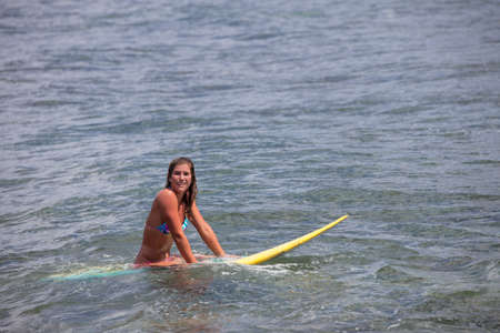 In Hawaii Pretty Young Woman on a Surfboard waiting for a wave 版權商用圖片
