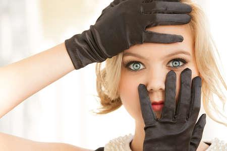 blonde yeux bleus: Jolie femme blonde encadrant ses yeux avec mains gantées de noir Banque d'images