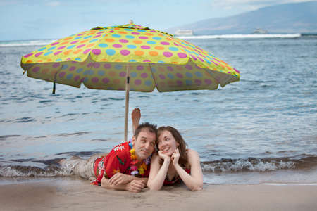 Loving couple  in matching outfits in the water with an Umbella in Hawaii photo