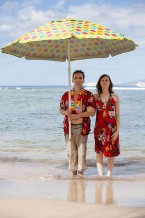 Couple holding an umbrella on the Beach in Hawaii with a contemplative look photo