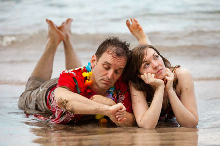 Tourist Couple on the Beach in Hawaii with a contemplative look photo