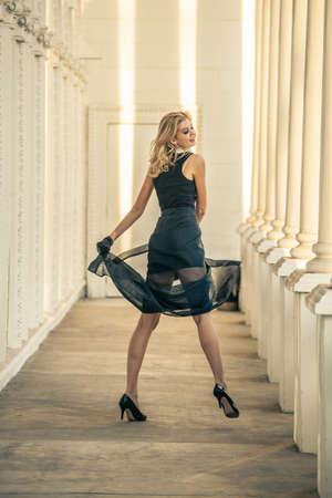 Blonde Beautiful woman wearing black in a gorgeous columned cathedral photo
