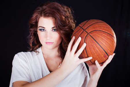 Beautiful Young woman holding a basketball looking at camera photo