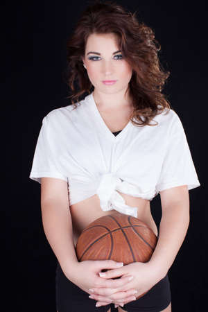 Pretty young brunette woman holding a basketball photo