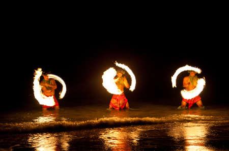 bailar�n: Tres hombres fuertes que hacen juegos malabares de fuego en Hawaii - bailarines de fuego Foto de archivo