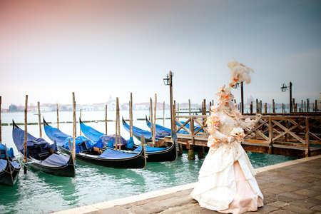 Sunrise in Venice Italy in front of Gondolas a Beautiful costumed woman Stockfoto