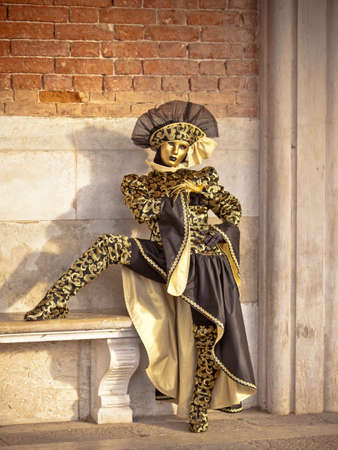 Hermoso de oro veneciano Carnaval maked Mujer por una pared de ladrillo antiguo photo