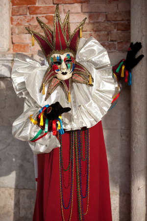 venice: Beautiful Golden Venetian Carnival Maked man hiding by an Ancient pillar  Stock Photo