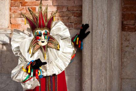 venice mask: Beautiful Golden Venetian Carnival Maked man hiding by an Ancient pillar  Stock Photo
