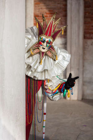 Beautiful Golden Venetian Carnival Maked man hiding by an Ancient pillar  Stockfoto