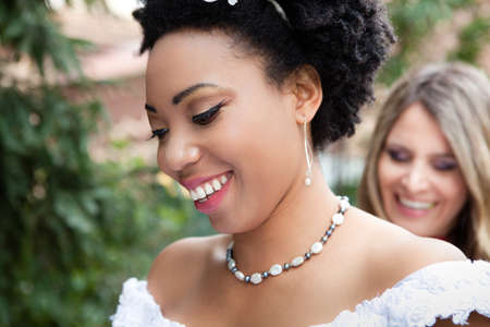 Beautiful Bride and her Makeup artist adjusting her dress