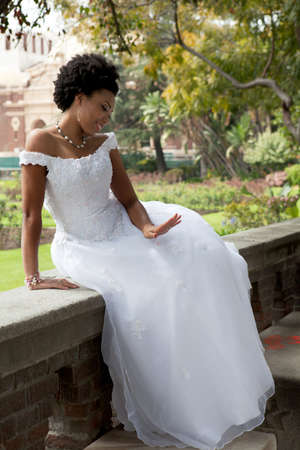 ethnic attire: Pretty African American Bride is smiling and Looking at her ring