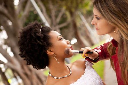 Beautiful Bride and her Makeup artist adjusting her eye shadow