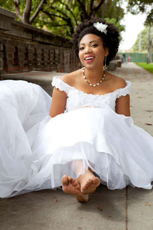 Pretty African American Bride is smiling sitting on the ground with Barefett photo