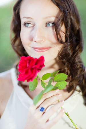 Pretty Woman with beautiful blue eyes and a red rose looking away Stock Photo - 17251754