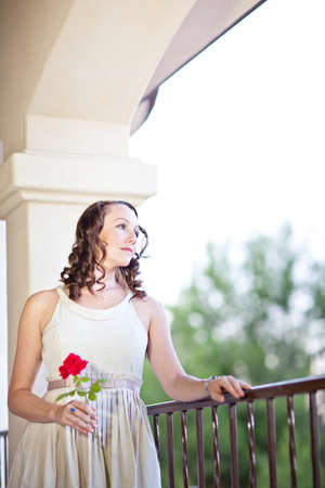 Pretty sad Woman with beautiful blue eyes and a red rose looking out Stock Photo - 17251797