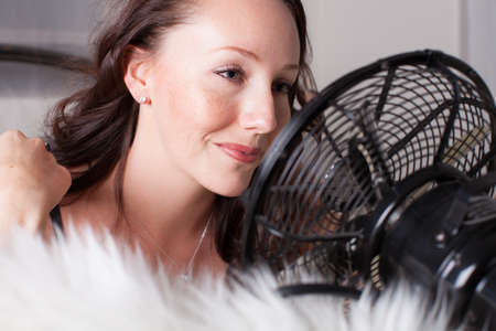 Beautiful sexy Woman cooling down with a fan