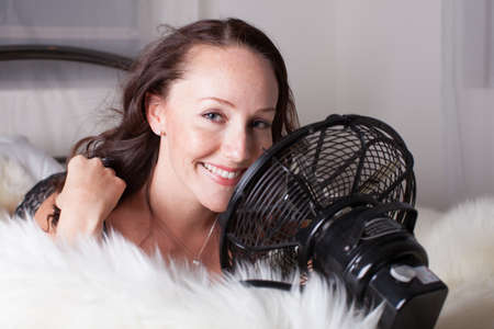 Beautiful sexy Woman cooling down with a fan in bed Archivio Fotografico