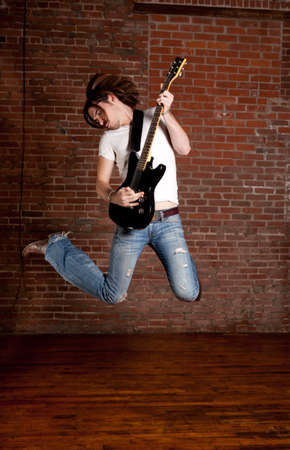 Male Guitar Player jumping with his electric guitar photo